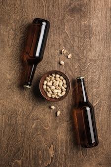Twee donkere bierflesjes en een plaat van pistachenoten op een houten achtergrond.
