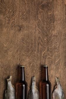 Twee donkere bierflesjes en gedroogde vis op een houten achtergrond. bovenaanzicht. copyspace.