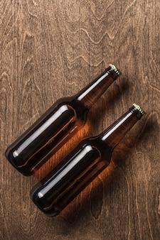 Twee donkere bierflesjes op een houten achtergrond. bovenaanzicht. kopieer ruimte.
