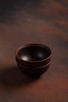 Twee donkere handgemaakte kleikommen op bruine tafel