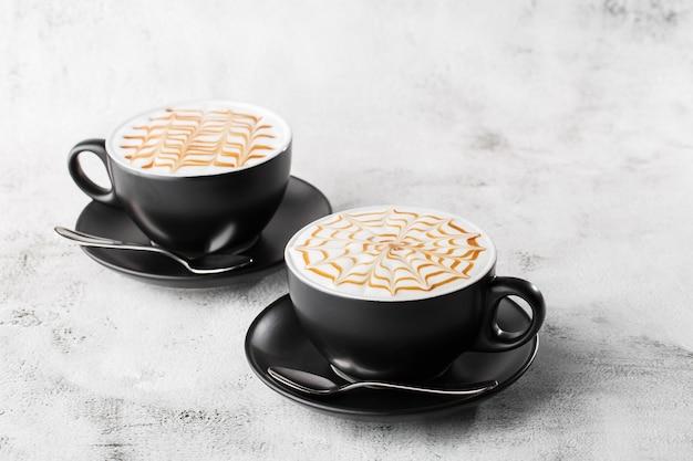 Twee donkere kopjes koffie met melk karamel latte kunst textuur geïsoleerd op heldere marmeren achtergrond. bovenaanzicht, kopieer ruimte. reclame voor café-menu. coffeeshop menu. horizontale foto.