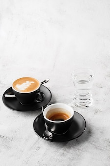 Twee donkere kopjes warme zwarte koffie, espresso, cappuccino met melk geïsoleerd op lichte marmeren achtergrond. bovenaanzicht, kopieer ruimte. reclame voor café-menu. coffeeshop menu. verticale foto.