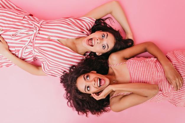 Twee donkere meisjes met prachtig haar en verbaasde gezichten poseren terwijl ze op hun rug liggen.