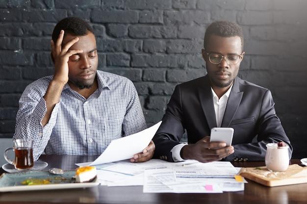 Twee donkere ondernemers zitten aan de tafel van het restaurant met papieren, voorbereid op belangrijke zakelijke bijeenkomst met potentiële partners, op zoek geconcentreerd. man in glazen met behulp van mobiele telefoon