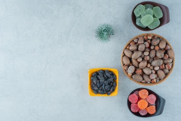 Twee donkere plaat van suikerconfituur met houten kom vol noten. hoge kwaliteit foto