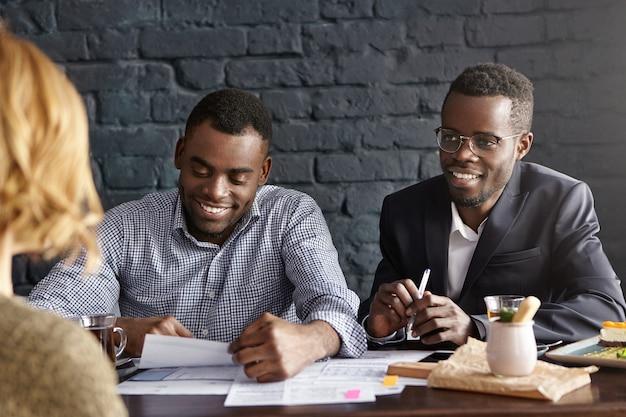 Twee donkere werkgevers die jonge vrouw met blond haar interviewen tijdens sollicitatiegesprek
