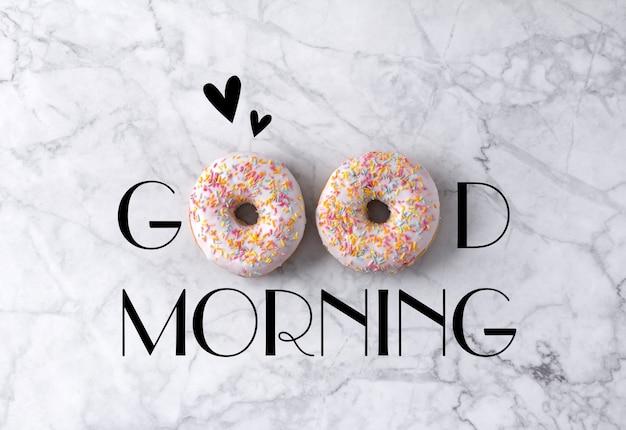 Twee donuts en harten. goedemorgengroet die op marmeren grijs wordt geschreven