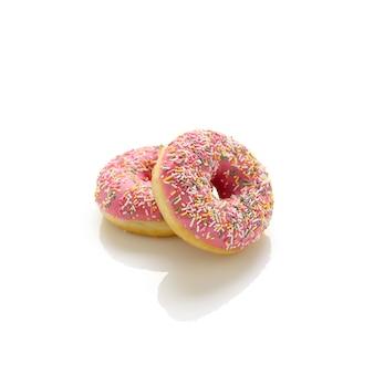 Twee donuts met roze suikerglazuur en gekleurde hagelslag op een witte achtergrond