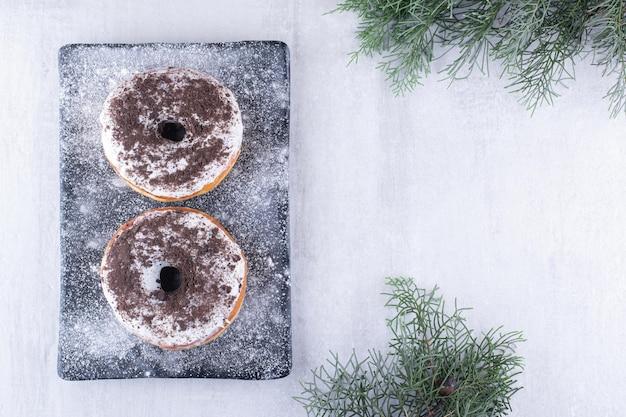Twee donuts op een met bloem bedekte schotel op een witte ondergrond
