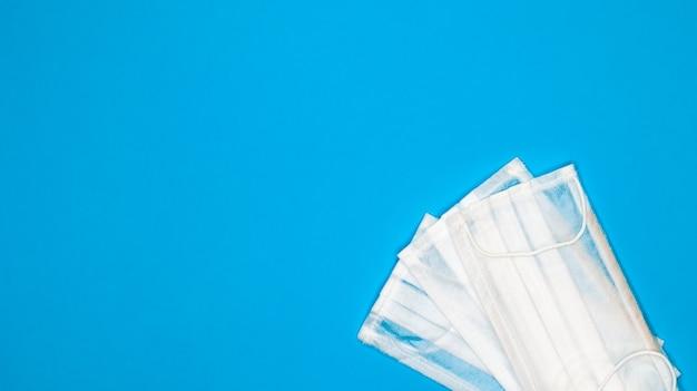 Twee drielaagse chirurgische gezichtsmaskers voor eenmalig gebruik met rubberen pads om de mond en neus te bedekken tegen een blauwe achtergrond. het concept van bescherming tegen bacteriën, gezondheidszorg en medicijnen. covid-19.
