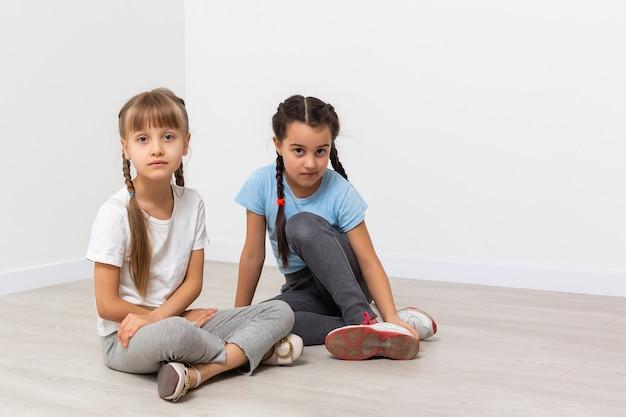 Twee droevige kleine meisjes, geïsoleerd over white