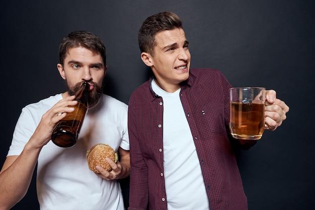Twee dronken vrienden bier drinken op een donkere achtergrond.