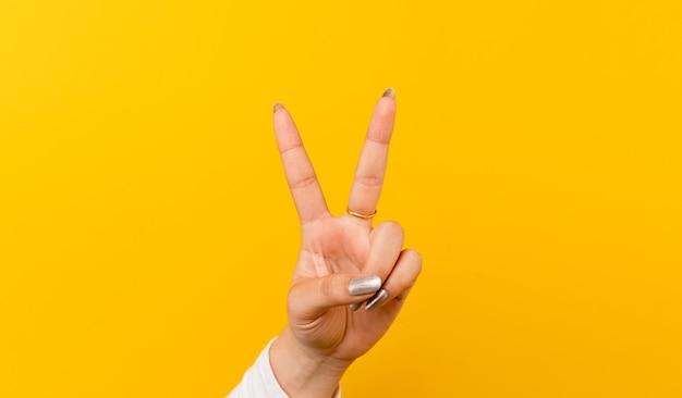 Twee duimen omhoog, de hand van het meisje op de gele achtergrond. toon strijd wederzijdse aanmoediging