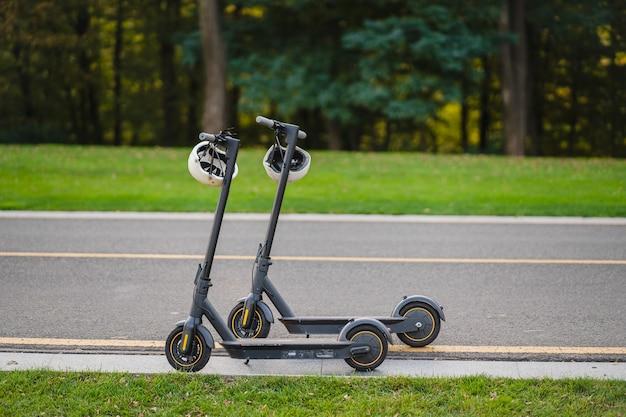 Twee e-scooters geparkeerd langs de zijlijnweg in het park