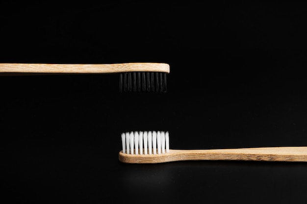 Twee eco-vriendelijke antibacteriële bamboe houten tandenborstels met witte en zwarte haren op een zwarte achtergrond.