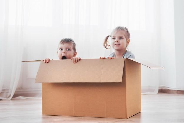Twee een kleine kinderen jongen en meisje spelen in kartonnen dozen. concept foto. kinderen hebben plezier