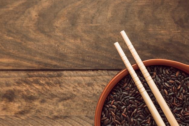 Twee eetstokjes over de zwarte kom van de rijstkorrel op houten achtergrond