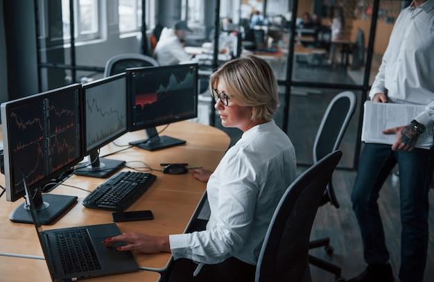 Twee effectenmakelaars in formele kleding werken op kantoor met financiële markt.