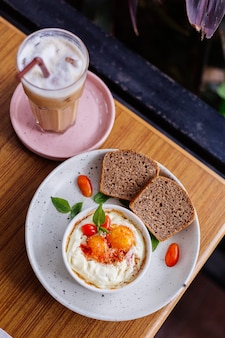 Twee eieren gebakken met ham en kaas in ronde kom twee stukjes bruin gezond brood aan de zijkant