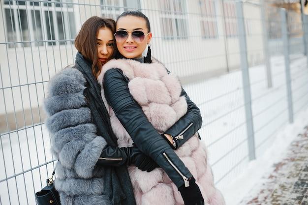 Twee elegante en prachtige meisjes in stijlvolle bontjassen wandelen in de winterstad