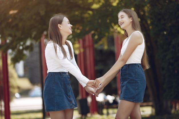 Twee elegante en stijlvolle meisjes in een lentepark
