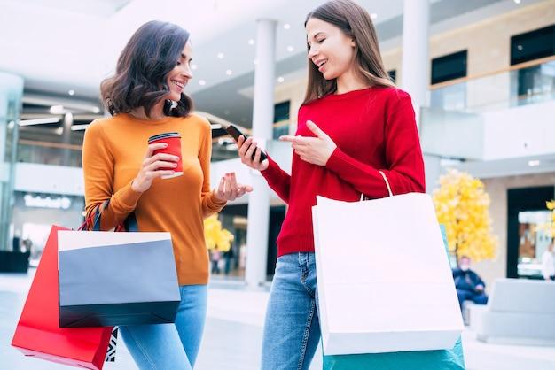 Twee elegante en stijlvolle mooie jonge vrouwen met boodschappentassen lopen in het winkelcentrum tijdens de uitverkoop van zwarte vrijdag