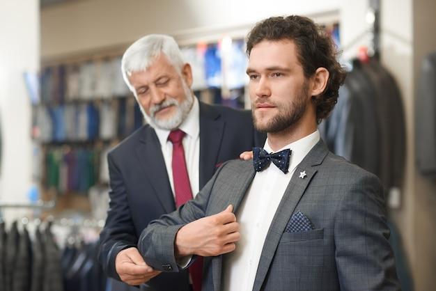 Twee elegante mannen komen naar de boetiek bij het winkelen.