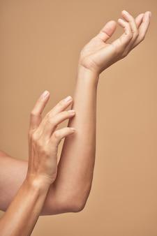 Twee elegante vrouwelijke handen met schoonheid naakt manicure in studio