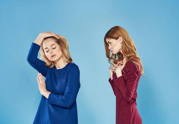 Twee elegante vrouwen beste vrienden levensstijl samen blauwe achtergrond. hoge kwaliteit foto