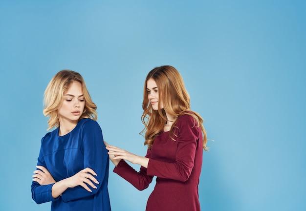 Twee elegante vrouwen beste vrienden levensstijl samen blauwe achtergrond