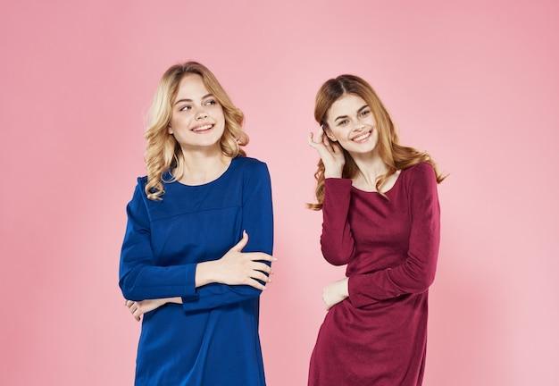 Twee elegante vrouwen communicatie de vriendschap roze achtergrond van de levensstijlstudio. hoge kwaliteit foto