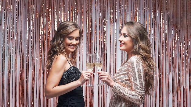 Twee elegante vrouwenvrienden in avondjurken die en champagne spreken drinken.