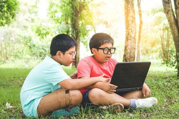 Twee elementaire aziatische kinderen zitten en leren computers bij het gazon in de tuin.