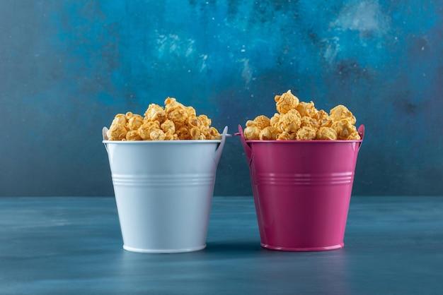 Twee emmers gevuld met caramel gecoate popcorn op blauw