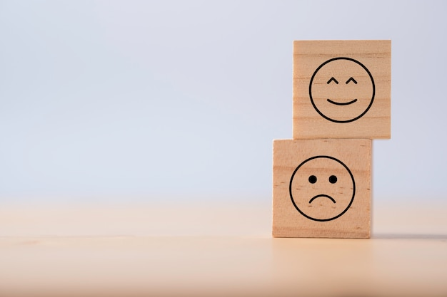 Twee emoties van blij en verdrietig die scherm afdrukken op houten kubieke. klantervaringsonderzoek en tevredenheidsfeedbackconcept.