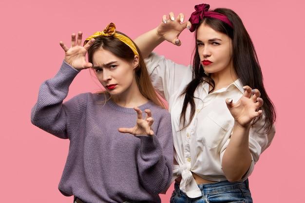 Twee emotionele boze jonge vrouwen fronsen en hand in hand alsof ze gaan aanvallen