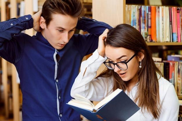 Twee emotionele studenten kijken samen in het boek, hand in hand bij hun hoofd