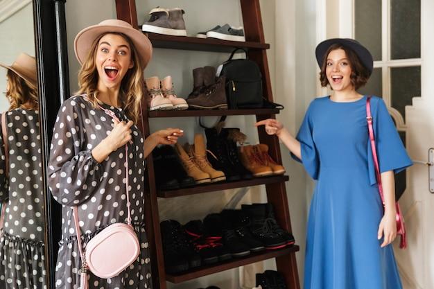 Twee emotionele verbazingwekkende jonge vrouwen die hoeden dragen die schoenen tonen.