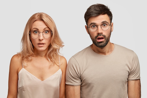 Twee emotionele verbijsterde jonge vrouw en man in nachtkleding, verslapen trein, staren naar de camera met verbaasde geschokte gezichtsuitdrukkingen