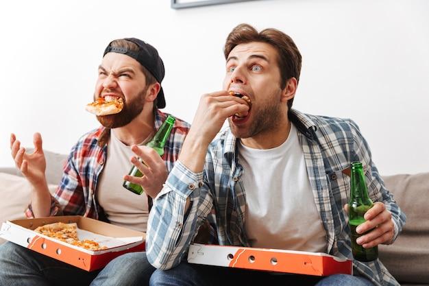 Twee emotionele vrijgezellen die plezier hebben in flat met pizza eten en bier drinken, terwijl ze tijdens het spel naar het voetbalteam wroeten
