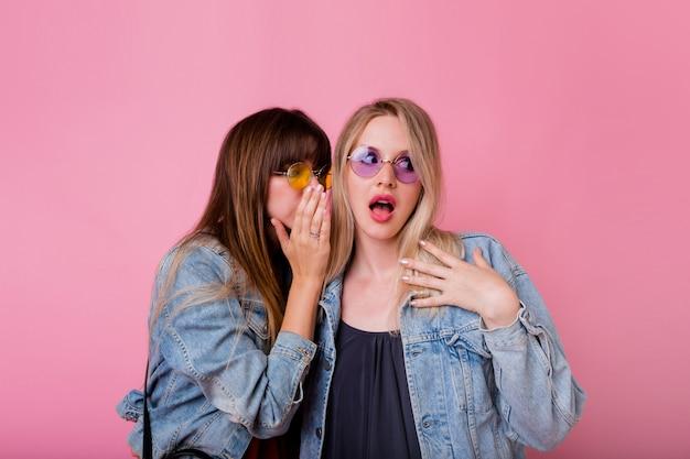 Twee emotionele vrouwen roddelen omhoog op roze muur