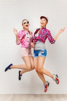 Twee en vrienden die stellen springen