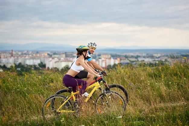 Twee energieke fietsers in helmen fietsen in hoog gras.