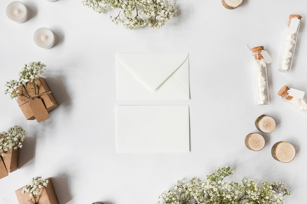 Twee envelop omringd met bloemen voor baby's; kaarsen; marshmallow reageerbuisjes; miniatuur boomstronken en geschenkdozen op witte achtergrond