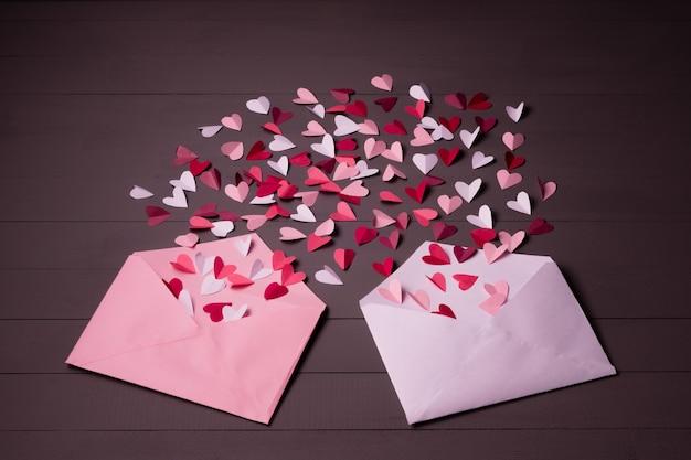 Twee enveloppen met papieren harten op grijze houten achtergrond. harten stijgen op van binnenuit open enveloppen. romantische liefdesbrieven.