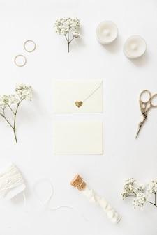 Twee enveloppen omringd met trouwringen; kaarsen; schaar; draad; reageerbuis en baby's-adem bloemen op witte achtergrond