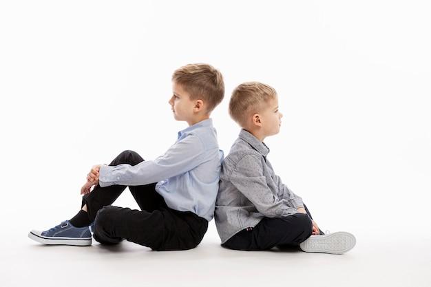 Twee ernstige leuke jongens zitten rug aan rug op een witte achtergrond. vriendschap en ondersteuning.