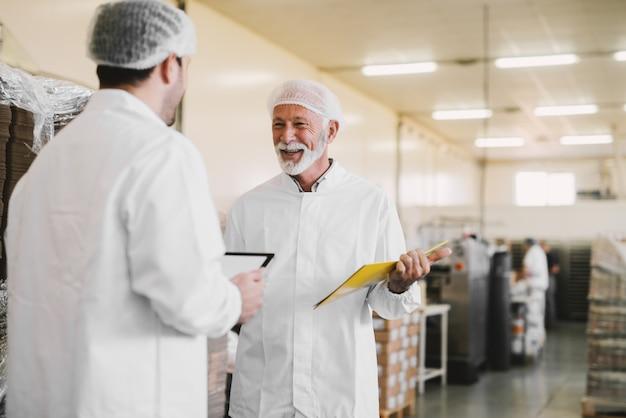 Twee ernstige zaken man in steriele kleren staan in voedselfabriek en praten over zaken. glimlachend en met documenten in hun handen.