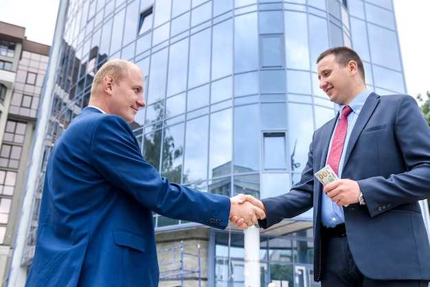 Twee ernstige zakenman poseren tegen zakencentrum
