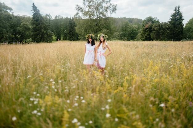 Twee etnische jonge meisjes met krans van bloemen poseren in veld.
